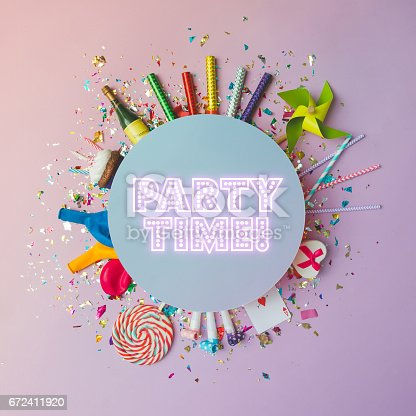 istock Colorful celebration background with various party confetti, balloons, streamers, fireworks and decoration on pink background. Flat lay. 672411920