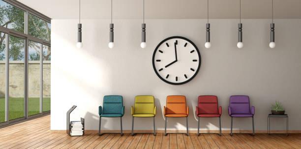 bunte stuhl in einem wartezimmer - uhrenhalter stock-fotos und bilder