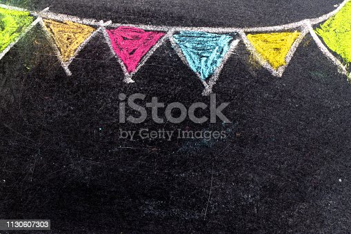 882318110 istock photo Colorful chalk drawing in hanging party flag shape on blackboard background 1130607303