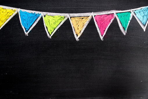 istock Colorful chalk drawing in hanging party flag shape on blackboard background 882318110