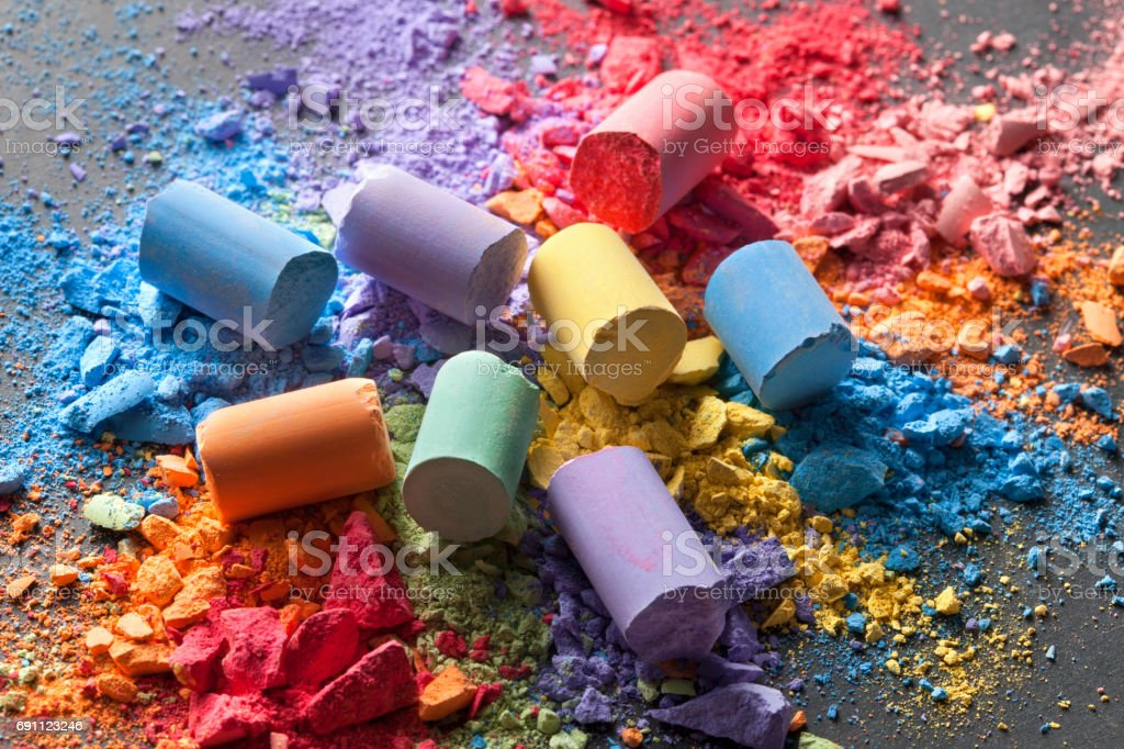 Colorful chalks with broken pastel particles on a blackboard stock photo