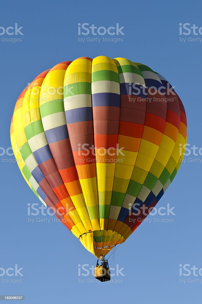 Colorful Checkered Hot Air Balloon Isolated on Blue Sky royalty-free stock photo