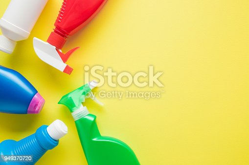 918825114 istock photo Colorful, chemical bottles for different surfaces cleaning in kitchen, bathroom and other rooms. Empty place for text or logo on yellow background. Cleaning service concept. Spring regular clean up. 949370720