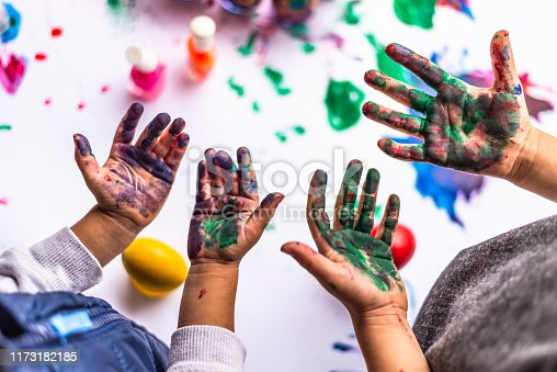 Close up of colorful children hands painting Easter eggs.