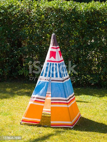 Colorful child's toy Teepee tent of native american made of canvas on the grass in a sunny day