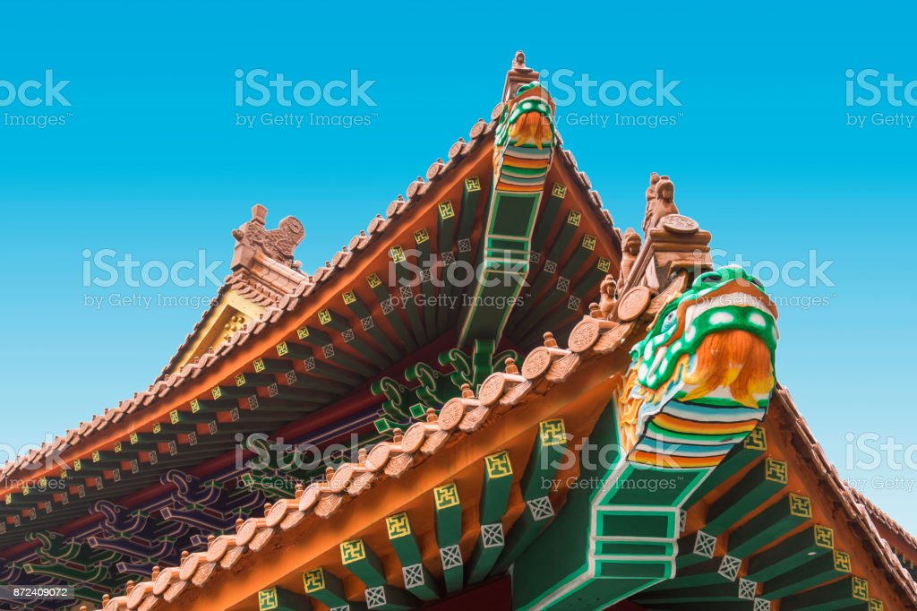Colorful chinese temple roof detail with a dragon and blue sky background. stock photo