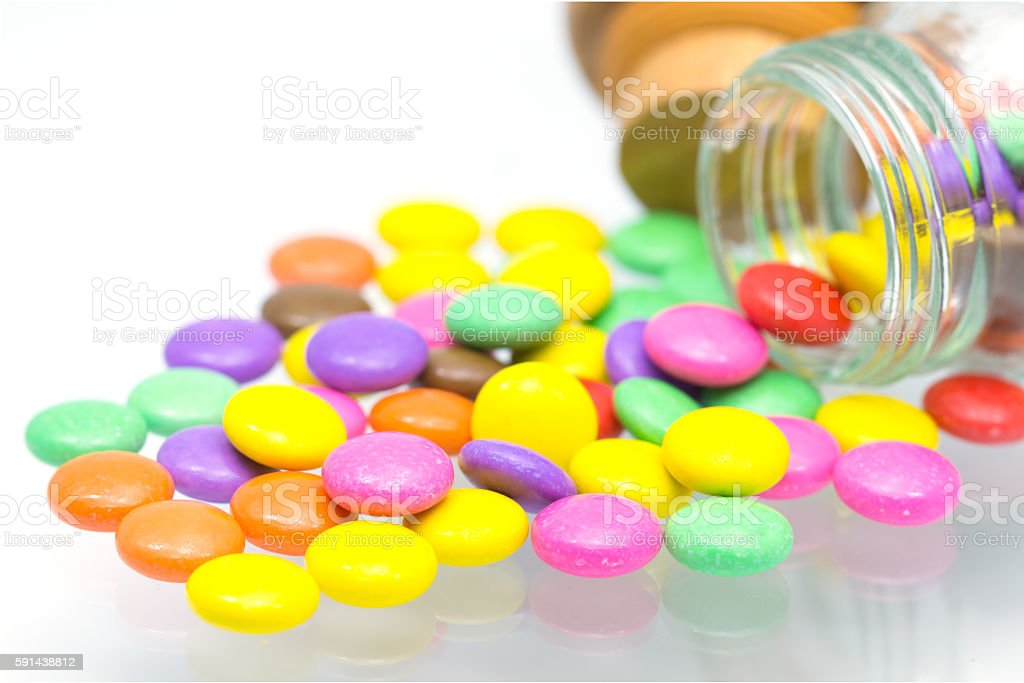 colorful chocolate coated candy pouring out of bottle  on white stock photo