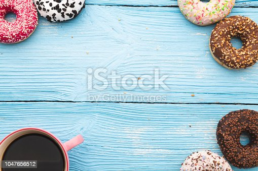 Coffee and chocolate donuts on blue wooden table with space on text. Top View