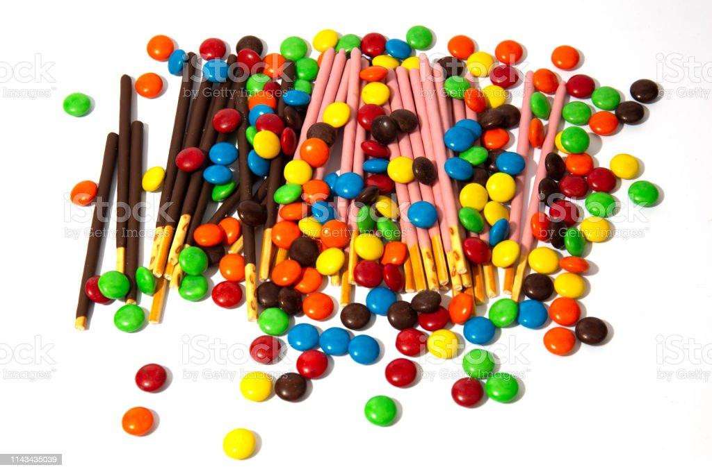 カラフルなチョコレートの Mms とポッキーのキャンディー白の背景に焦点を当てて おやつのストックフォトや画像を多数ご用意 Istock
