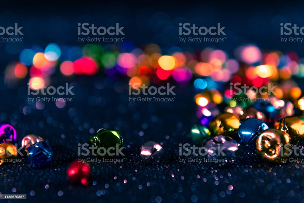Colorful Christmas jingle bells. Blue filter. Blurred bokeh background. Colorful Christmas jingle bells. Blue filter applied. Blurred bokeh glitter background. Shallow depth of field. For overlay, background or texture. Backgrounds Stock Photo
