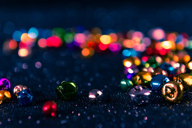 Colorful Christmas jingle bells. Blue filter. Blurred bokeh background. stock photo