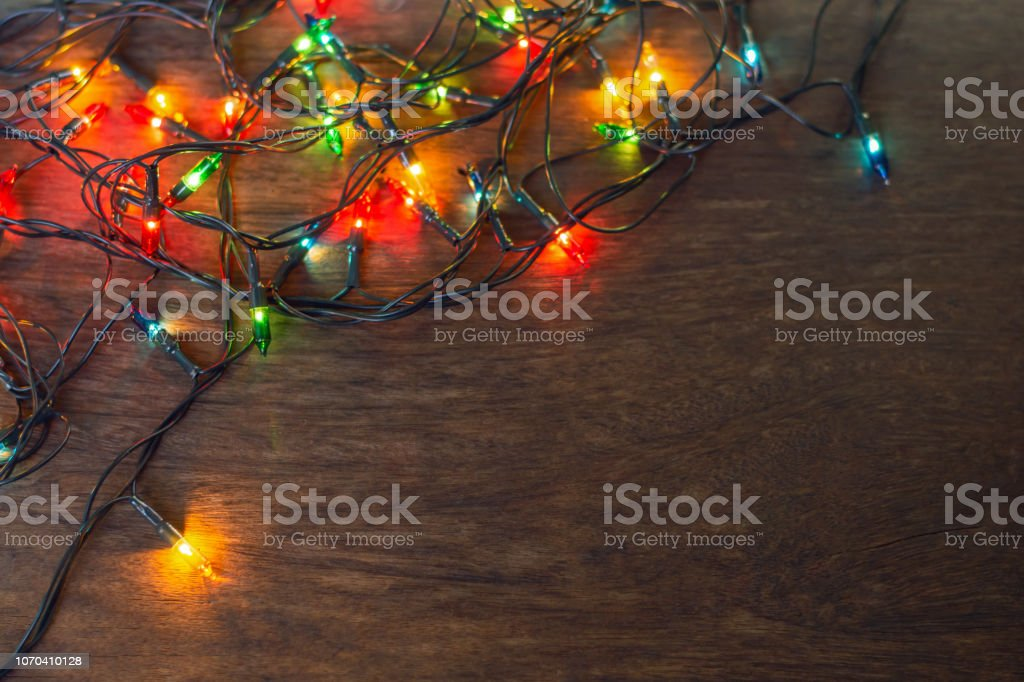 Colorful Christmas Lights Background.Colorful Christmas Lights Over Dark Wooden Background Flat