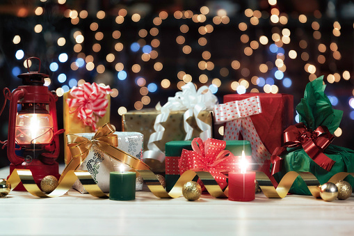 Colorful Christmas presents on defocused Christmas lighting background with copy space