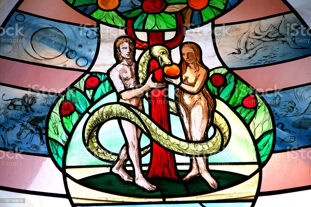 colorful church window with adam and eve stock photo