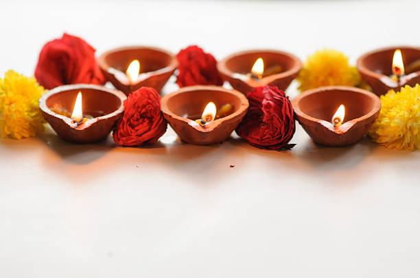 Colorful clay diya lamps lit during diwali celebration stock photo