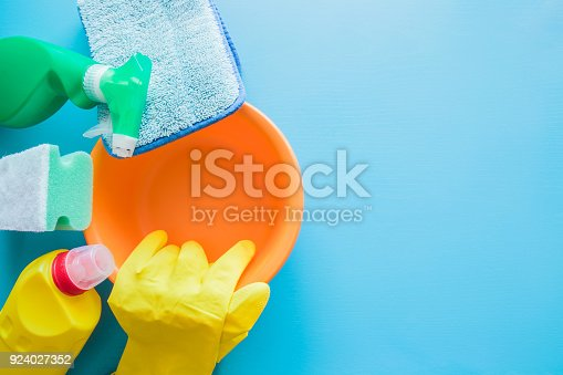 918825114 istock photo Colorful cleaning set for different floor surfaces in kitchen, bathroom and other rooms. Empty place for text or logo on blue background. Cleaning service concept. Early spring regular clean up. 924027352