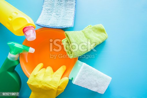 918825114 istock photo Colorful cleaning set for different surfaces and floors in kitchen, bathroom and other rooms. Blue background. Cleaning service concept. Early spring regular clean up. 925219612