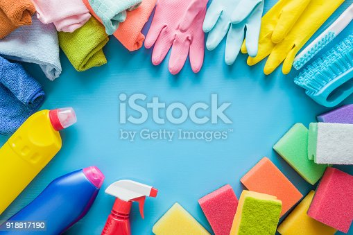918825114 istock photo Colorful cleaning set for different surfaces in kitchen, bathroom and other rooms. Empty place for text or logo on blue background. Cleaning service concept. Early spring regular clean up. Top view. 918817190