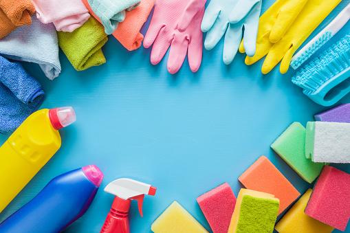 istock Colorful cleaning set for different surfaces in kitchen, bathroom and other rooms. Empty place for text or logo on blue background. Cleaning service concept. Early spring regular clean up. Top view. 918817190