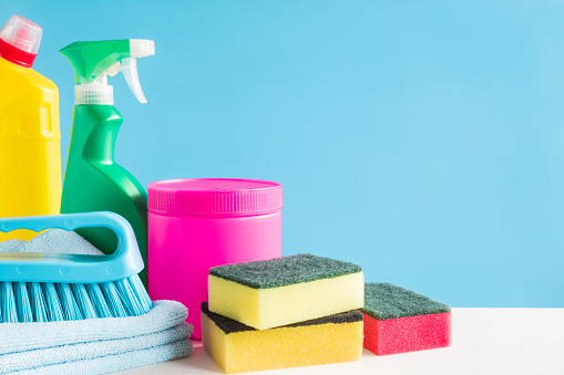 istock Colorful cleaning set for different surfaces in kitchen, bathroom and other rooms. Empty place for text or logo on blue background. Cleaning service concept. Early spring regular clean up. Front view. 918824602