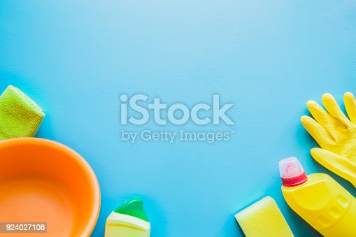 918825114 istock photo Colorful cleaning set for different surfaces in kitchen, bathroom and other rooms. Empty place for text or logo on blue background. Cleaning service concept. Early spring regular clean up. Top view. 924027108