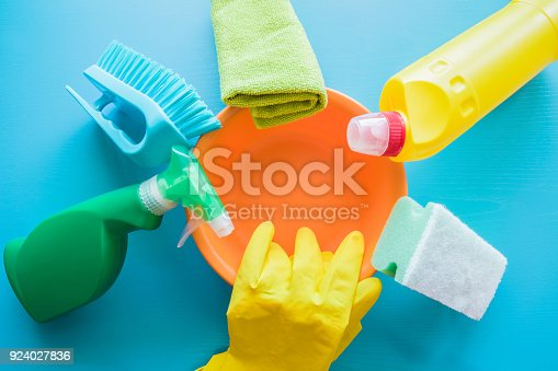 918825114 istock photo Colorful cleaning set for different surfaces in kitchen, bathroom and other rooms.  Cares about house cleanliness. Cleaning service concept. Early spring regular clean up. Blue background. Top view. 924027836