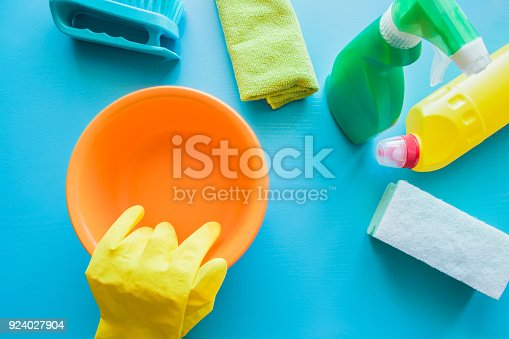 918825114 istock photo Colorful cleaning set for different surfaces in kitchen, bathroom and other rooms.  Cares about house cleanliness. Cleaning service concept. Early spring regular clean up. Blue background. Top view. 924027904