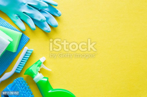 918825114 istock photo Colorful cleaning set for different surfaces in kitchen, bathroom and other rooms. Empty place for text or logo on yellow background. Cleaning service concept. Early spring regular clean up. Top view. 931126152