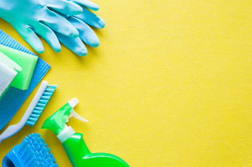 istock Colorful cleaning set for different surfaces in kitchen, bathroom and other rooms. Empty place for text or logo on yellow background. Cleaning service concept. Early spring regular clean up. Top view. 931126152