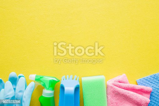 918825114 istock photo Colorful cleaning set for different surfaces in kitchen, bathroom and other rooms. Empty place for text or logo on yellow background. Cleaning service concept. Early spring regular clean up. Top view. 932323256