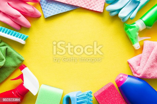 918825114 istock photo Colorful cleaning set for different surfaces in kitchen, bathroom and other rooms. Empty place for text or logo on yellow background. Cleaning service concept. Early spring regular clean up. Top view. 932323384