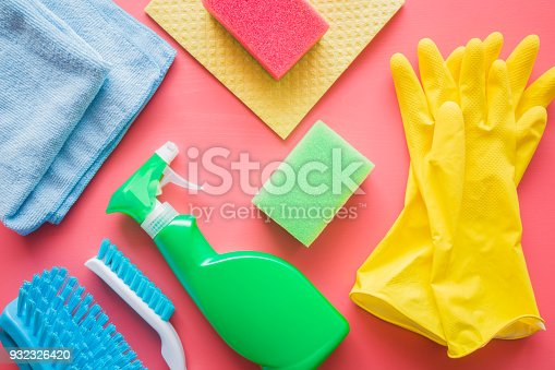 918825114 istock photo Colorful cleaning set for different surfaces in kitchen, bathroom and other rooms. Cares about house cleanliness. Cleaning service concept. Early spring regular clean up. Pink background. Top view. 932326420