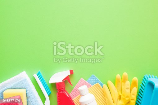918825114 istock photo Colorful cleaning set for different surfaces in kitchen, bathroom and other rooms. Empty place for text or logo on green background. Cleaning service concept. Spring regular clean up. Top view. 946877174