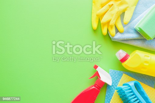 918825114 istock photo Colorful cleaning set for different surfaces in kitchen, bathroom and other rooms. Empty place for text or logo on green background. Cleaning service concept. Spring regular clean up. Top view. 946877244