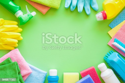 918825114 istock photo Colorful cleaning set for different surfaces in kitchen, bathroom and other rooms. Empty place for text or logo on green background. Cleaning service concept. Spring regular clean up. Top view. 946877332
