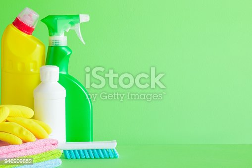 918825114 istock photo Colorful cleaning set for different surfaces in kitchen, bathroom and other rooms. Empty place for text or logo on green background. Cleaning service concept. Spring regular clean up. Front view. 946909682
