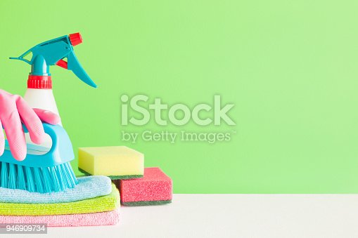 918825114 istock photo Colorful cleaning set for different surfaces in kitchen, bathroom and other rooms. Empty place for text or logo on green background. Cleaning service concept. Spring regular clean up. Front view. 946909734