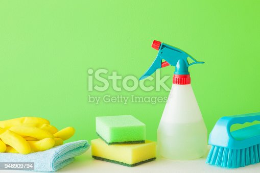 918825114 istock photo Colorful cleaning set for different surfaces in kitchen, bathroom and other rooms. Empty place for text or logo on green background. Cleaning service concept. Spring regular clean up. Front view. 946909794