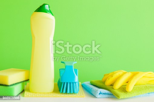 918825114 istock photo Colorful cleaning set for different surfaces in kitchen, bathroom and other rooms. Empty place for text or logo on green background. Cleaning service concept. Spring regular clean up. Front view. 946909866