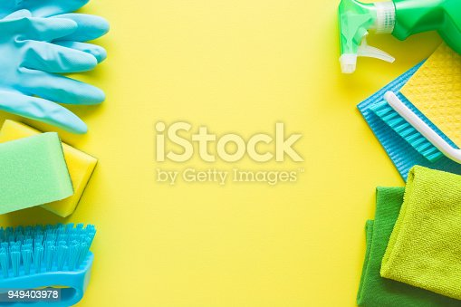 918825114 istock photo Colorful cleaning set for different surfaces in kitchen, bathroom and other rooms. Empty place for text or logo on yellow background. Cleaning service concept. Early spring regular clean up. Top view. 949403978