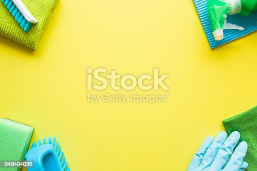 918825114 istock photo Colorful cleaning set for different surfaces in kitchen, bathroom and other rooms. Empty place for text or logo on yellow background. Cleaning service concept. Early spring regular clean up. Top view. 949404036