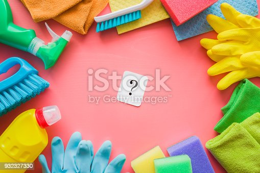 istock Colorful cleaning set for different surfaces in rooms, kitchen and bathroom. Question mark on pink background. Early spring regular clean up. What kind of supplies housewife choose for house care. 932327330