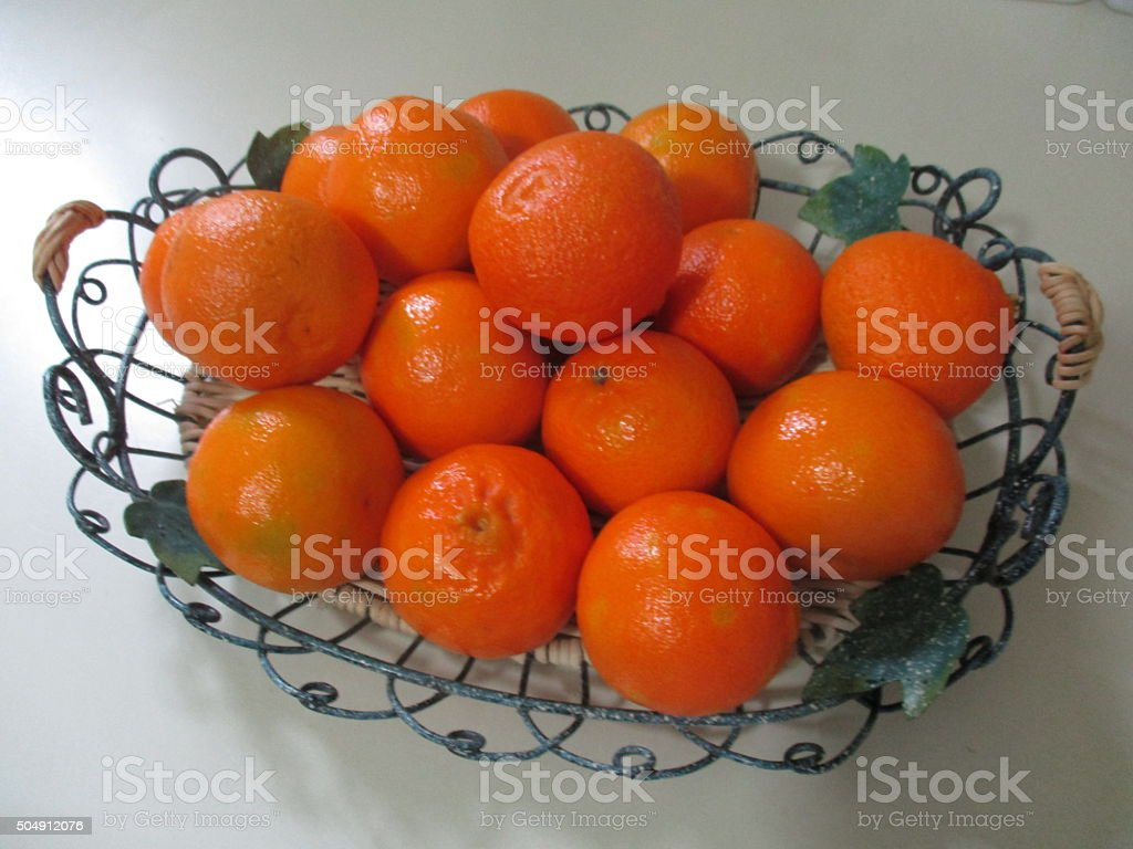 Colorful Clementines in a Green Wire Basket stock photo