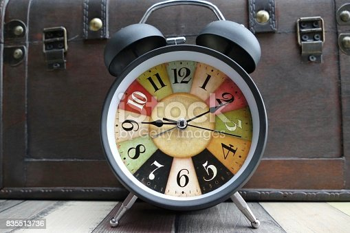 Colorful clock in standing at a wooden treasure box