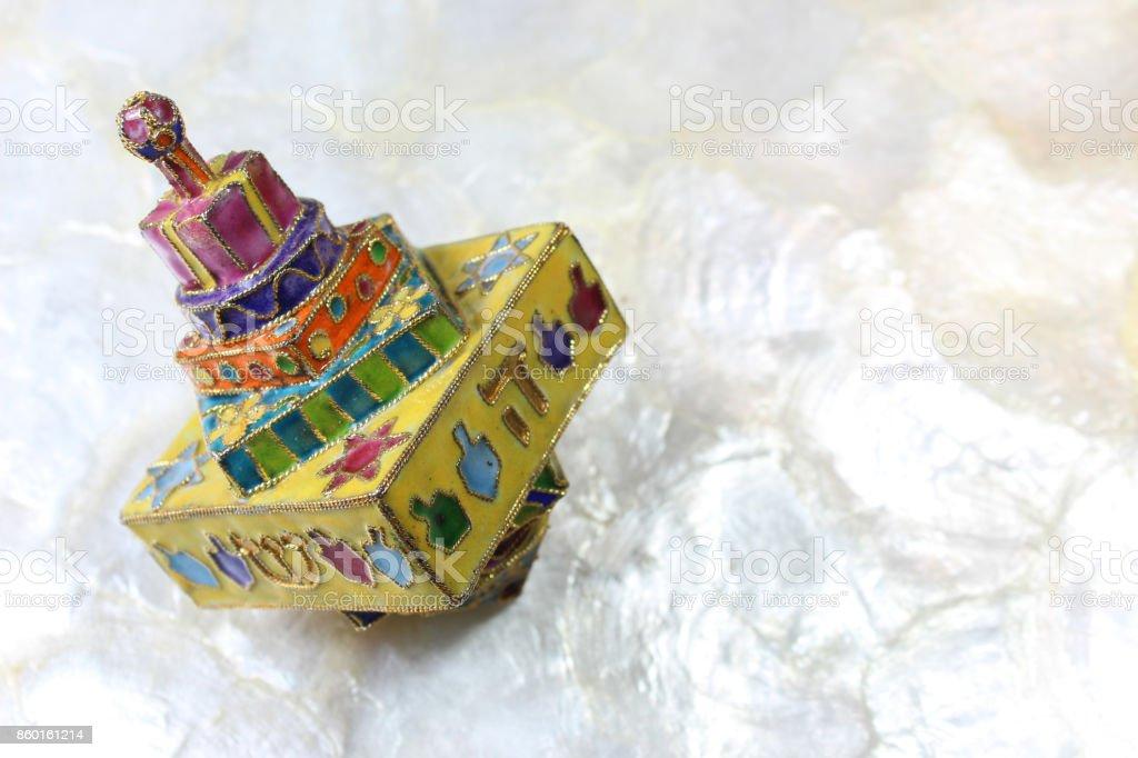 Colorful cloisonne Hanukkah dreidel on soft white background, space for text stock photo