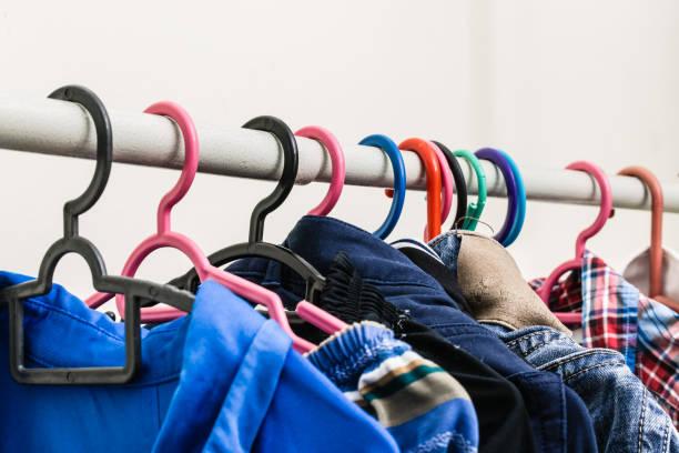 bunte tuch hängt an kleiderständer nahaufnahme - spenden sammeln stock-fotos und bilder