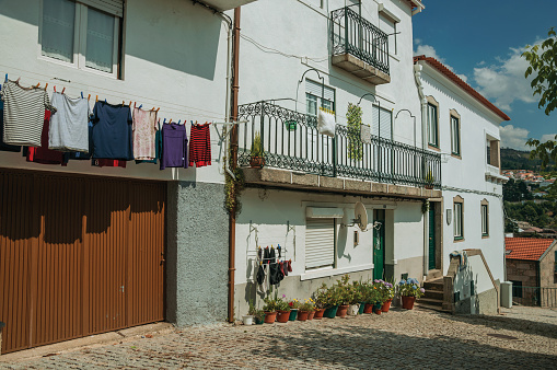Gouveia, Portugal - July 17, 2018. Colorful clothes hung to dry in front of building with whitewashed wall in Gouveia. A nice country town with gardens and captivating historical heritage in Portugal.