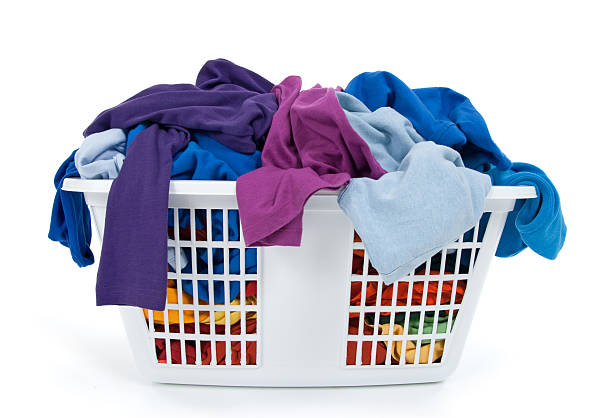 Colorful clothes in laundry basket. Blue, indigo, purple. stock photo