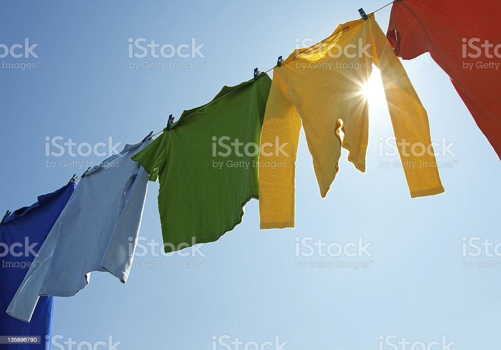 Colorful clothes on a laundry line and sun shining stock photo