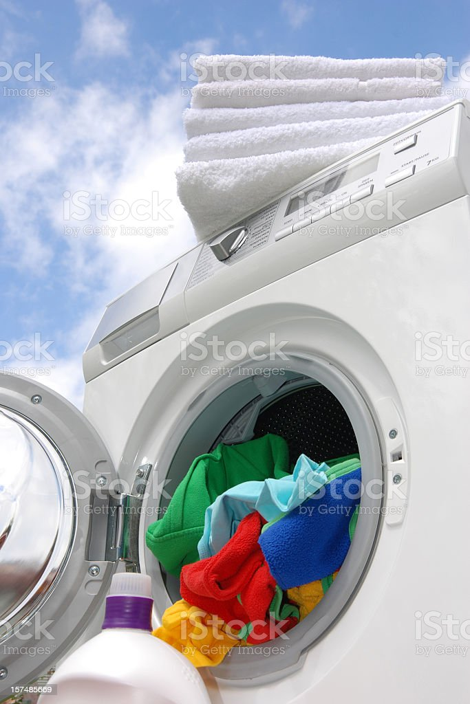 Colorful clothes on an open upright washing machine royalty-free stock photo
